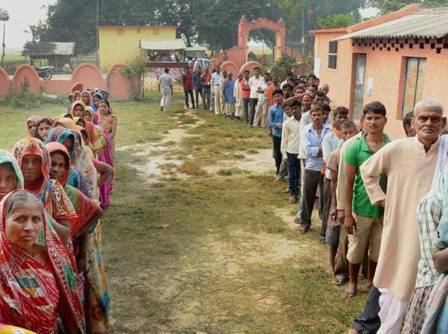 People wait in queues to cast their votes during the fifth phase of Bihar elections, in Madhepura.