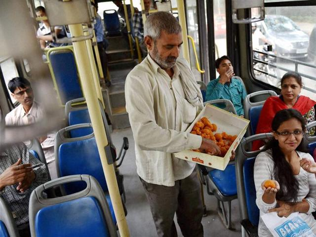 A JD(U) supporter distributes sweets in a DTC bus after party's win in the Bihar assembly elections, in New Delhi.