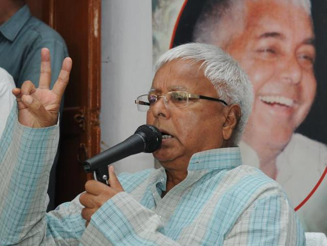 RJD chief Lalu Prasad shows victory signs during a press conference in Patna.