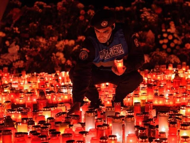 A Romanian gendarme places candles given by the people who came to pay respect for the victims of the fire at the