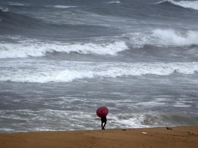 A fisherman stands on the Bay of Bengal coast during high tide in Chennai.