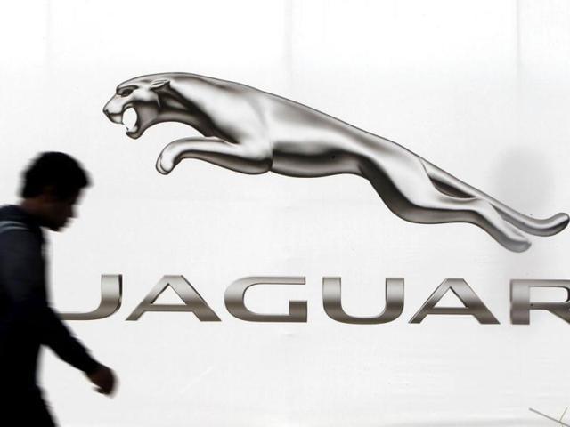 A man walks past a billboard advertising Jaguar in New Delhi.