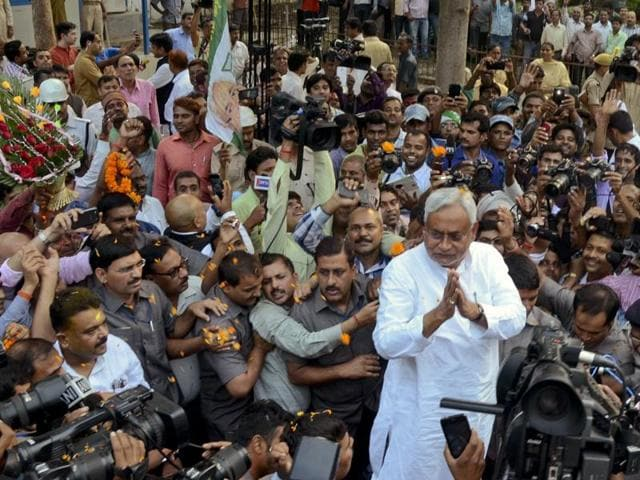 Bihar chief minister Nitish Kumar is surrounded by media persons as he greets supporters after the Grand Alliance's victory in the state elections, in Patna.