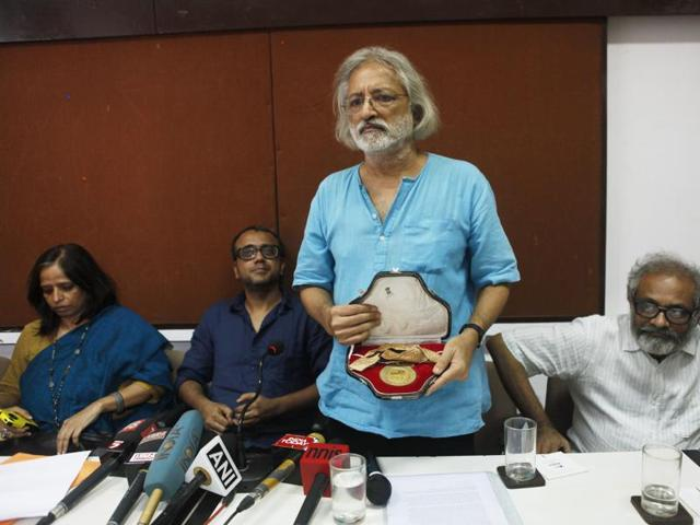 Filmmaker Anand Patwardhan showing his national award which he returned in protest against the growing intolerance around the nation and the unsolved FTII issue.(HT Photo)