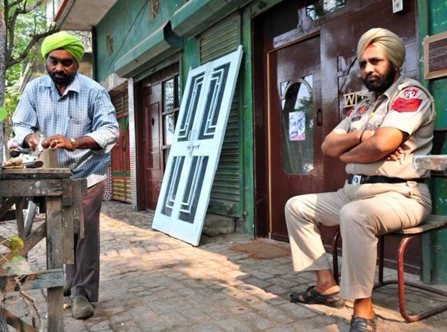 A cop guards the house of dera follower Raghbir Singh Insan at Bhanglan in Samrala.