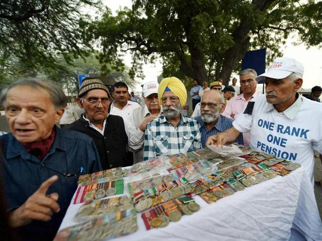 Ex-servicemen return their medals to deputy collector during their agitation for One Rank One Pension (OROP) scheme benefits and privileges near the IGI airport in New Delhi on Tuesday.