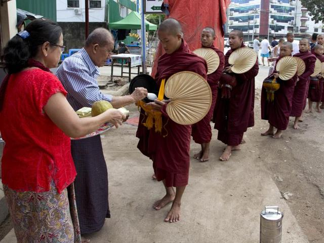 Buddhist monks receive offerings of rice from a shopkeeper in Myanmar.