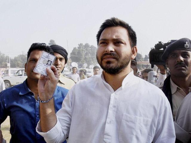 RJD leader Tejashwi Yadav shows his voter card at a polling station during third phase of Bihar assembly elections in Patna.
