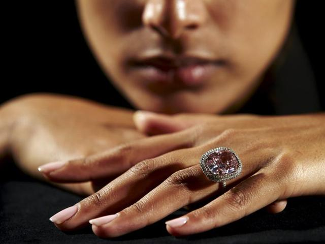 An employee poses with a cushion-shaped 16.08 carat vivid pink diamond at Christie's auction house in Geneva.