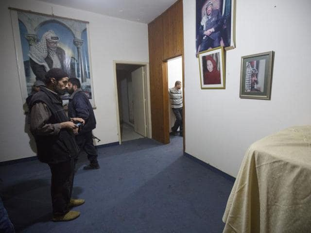 Palestinians take photos of the clothes of former Palestinian president Yasser Arafat, in the bedroom of his house.