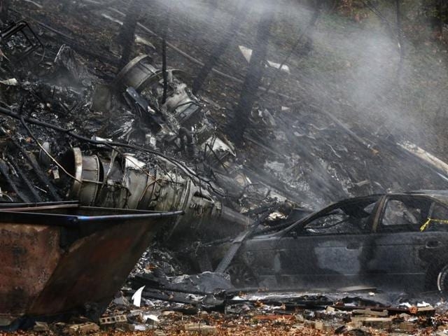 A charred car and aircraft debris smoulder where authorities say a small business jet crashed into an apartment building in Akron, Ohio.