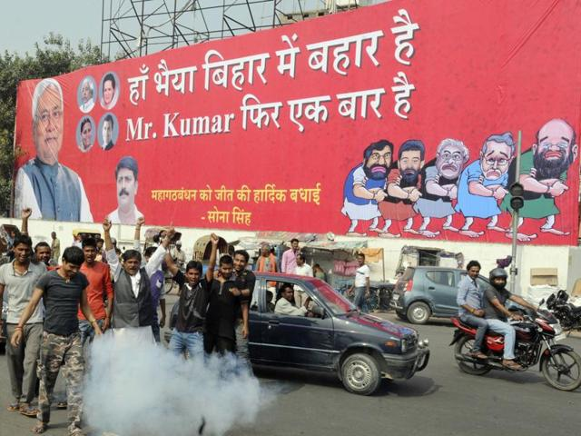 A huge poster is put up as Grand Alliance supporters celebrate at chief minister Nitish Kumar's residence on the counting day of the Bihar Assembly elections, in Patna.