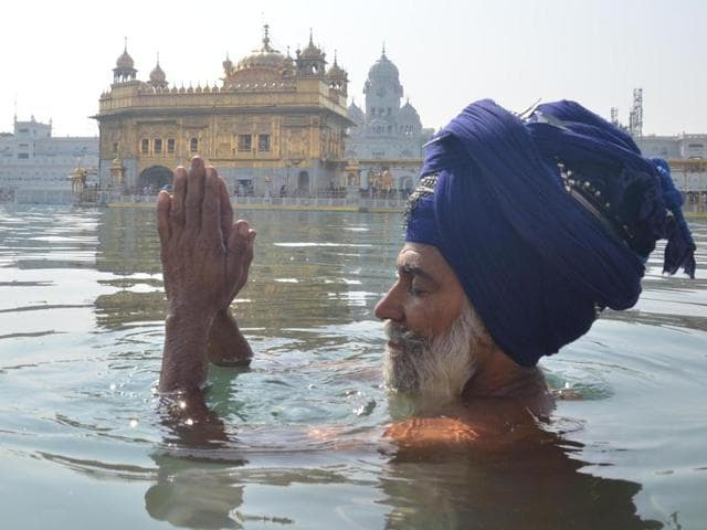 A Sikh devotee taking dip in the Sarovar of the Golden Temple on the occasion of Diwali.