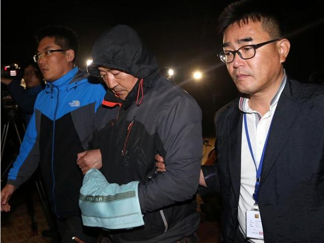 Lee Joon-seok, center, the captain of the sunken ferry Sewol in the water off the southern coast, leaves a court which issued his arrest warrant in Mokpo, south of Seoul, South Korea.