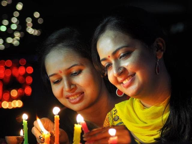 Women lighting candles during Diwali in Sector 19 on Wednesday.