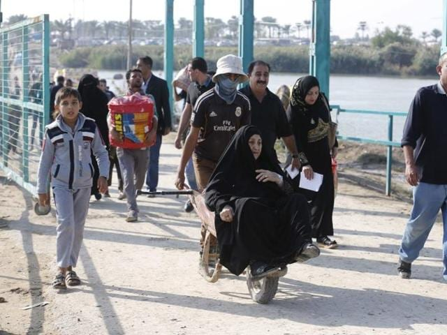Displaced Sunni people fleeing the violence, cross a bridge on the outskirts of Baghdad.