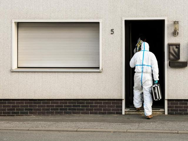 A police investigator in protective cloth enter a house in Wallenfels, southern Germany.