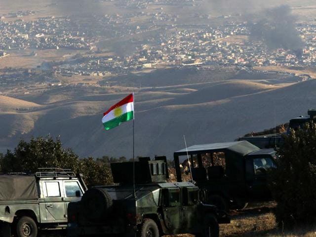 Iraqi Kurdish forces are seen stationed on a hill top as smoke billows during an operation by them (backed by US-led strikes) in the northern Iraqi town of Sinjar.