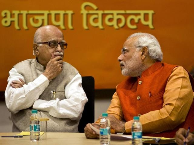 BJP leader Lal Krishna Advani listens to Narendra Modi, during a meeting in New Delhi, India, in this December 8, 2013 file photo.