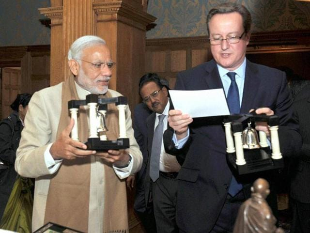 Prime Minister Narendra Modi presenting a gift to the Prime Minister of United Kingdom (UK), David Cameron in London on Friday.