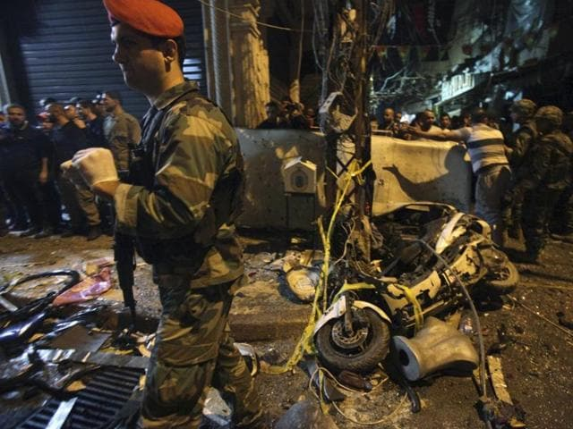 A man walks near a blood stain in a damaged area caused by two explosions in Beirut's southern suburbs, Lebanon.