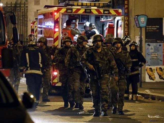 Soldiers walk in front of an ambulance as rescue workers evacuate victims near La Belle Equipe, rue de Charonne.