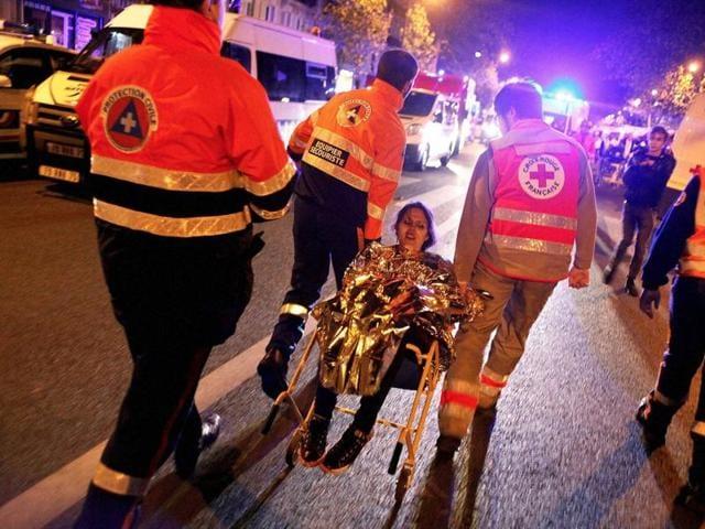 A person is being rescued after a shooting outside the Bataclan theater in Paris. A series of attacks targeting young concert-goers, soccer fans and Parisians enjoying a Friday night out at popular nightspots killed over 100 people.