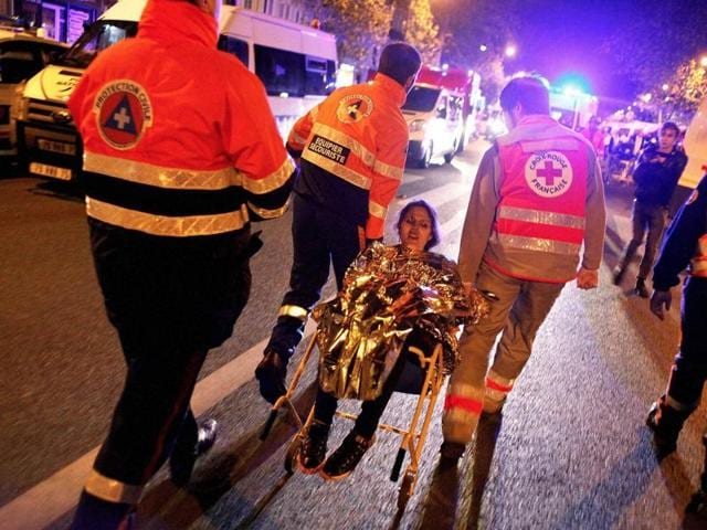 A person is evacuated after a shooting outside the Bataclan theater in Paris on November 14, 2015. A series of attacks targeting young concert-goers, soccer fans and Parisians enjoying a Friday night out at popular nightspots killed over 100 people in the deadliest violence to strike France since World War II.