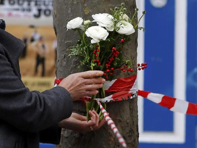 A man puts flowers near the French embassy to commemorate victims of attacks in Paris.