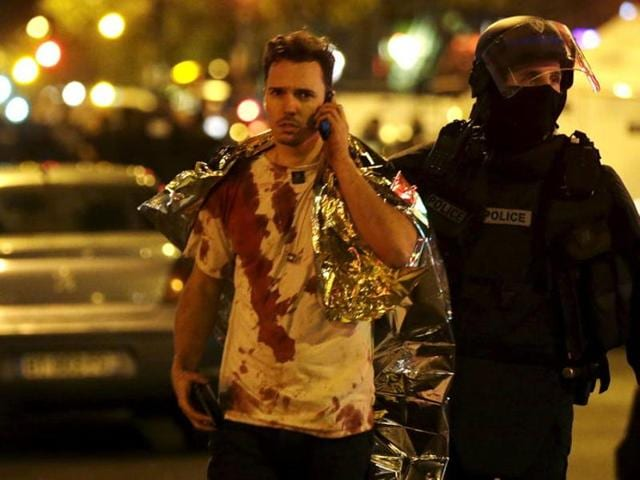 A French policeman assists a blood-covered victim near the Bataclan concert hall following attacks in Paris.