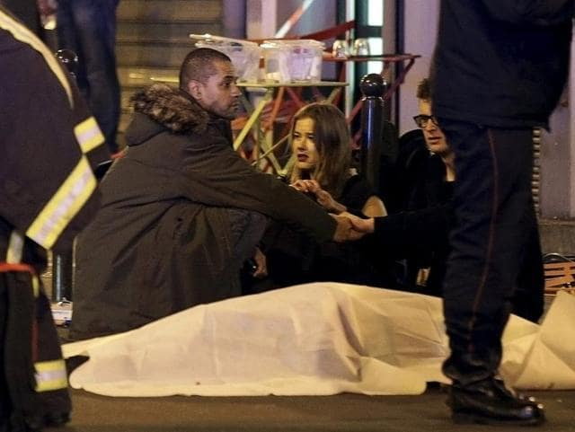Rescue services personnel working near the covered bodies outside a restaurant following a shooting incident in Paris.