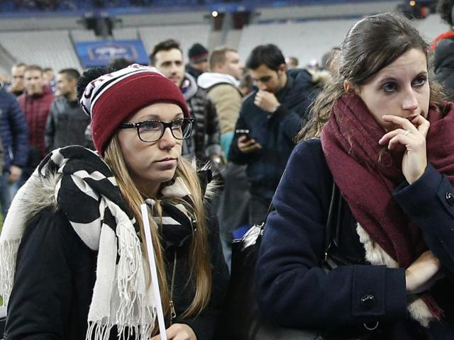 Soccer fans wait on the fitch of the Stade de France stadium after an international friendly soccer match in Saint Denis, outside Paris. An explosion occurred outside the stadium.