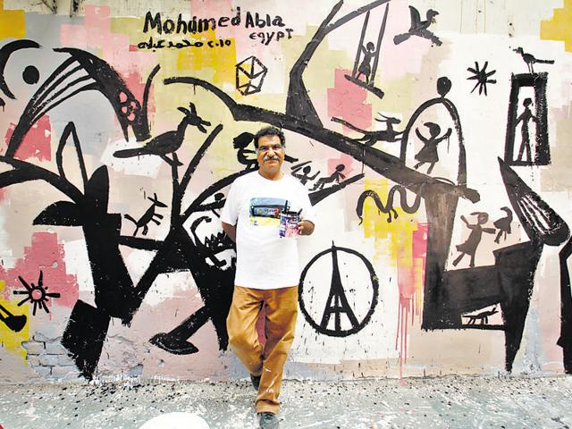 Egyptian artist Mohamed Abla with his work on the walls of Khan Market on Saturday.