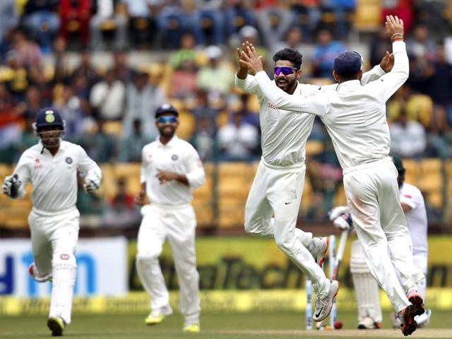 India's Ravindra Jadeja and captain Virat Kohli celebrate the dismissal of South Africa's Dean Elgar on the first day of the second Test at the M Chinnaswamy Stadium in Bengaluru on November 14, 2015.