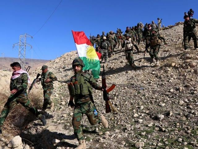 Iraqi autonomous Kurdish region's peshmerga forces and fighters from the Yazidi minority, a local Kurdish-speaking community which the Islamic State (IS) group had brutally targeted in the area, hold a Kurdish flag while entering the northern Iraqi town of Sinjar. Iraqi Kurdish leader Massud Barzani announced the