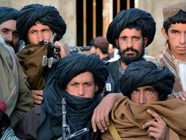 File photo of Afghan Taliban fighters listening to Mullah Mohammed Rasool, unseen, the newly-elected leader of a breakaway faction of the Taliban, in Farah province, Afghanistan.  The faction said on Saturday, November 14, 2015, that its deputy leader Mullah Mansoor Dadullah is 'seriously wounded' but still alive, denying reports of   him being killed battling rival insurgents.