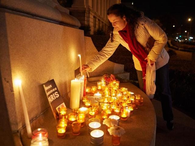 People take part in a candle light vigil in St. Louis, Missouri, a day after the terrorist attacks in Paris.