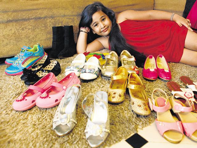 Ziya D'Souza, 6, poses with some of her shoes. At last count, she had 15 pairs of footwear, six bags, and a wardrobe that contained a number of net tops and gowns. 'She loves to shop and has a big fetish for shoes and bags,' says her mother, Esther, an entrepreneur. Ziya was also among the models who walked the ramp at India Kids Fashion Week, in Mumbai.