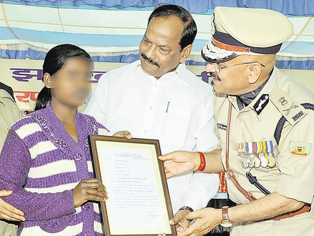Chief minister Raghubar Das talks to former Maoist Balmuni after giving her appointment letter for the post of 'child constable' in state police during a function on the eve of Statehood day at JAP-1 ground in Ranchi.