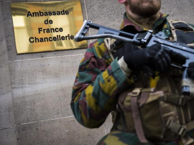 A soldier stands guard outside the French embassy the day after a string of attacks in Paris, in Brussels.