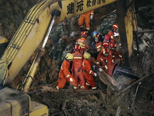 In this Saturday, Nov. 14, 2015 photo, rescuers remove a body found in the aftermath of a landslide in Lishui in east China's Zhejiang province.(AP Photo)