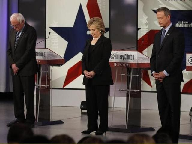 Democratic US presidential candidates Senator Bernie Sanders (L), former secretary of state Hillary Clinton and former Maryland Governor Martin O'Malley bow their heads in a moment of silence for the recent attacks in Paris ahead of the second official 2016 US Democratic presidential candidates debate in Des Moines, Iowa.