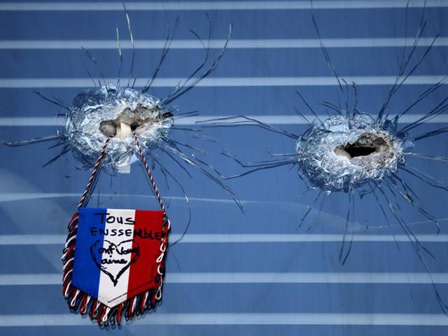 A French flag hangs from broken glass from a bullet hole in the window of the restaurant on Rue de Charonne, Paris.