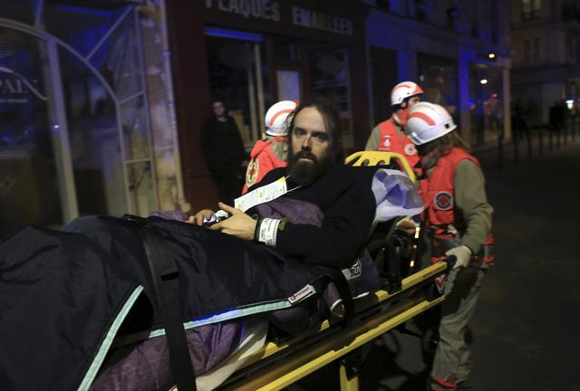 A man is evacuated from the Bataclan theater after the attacks in Paris on November 13, 2015.