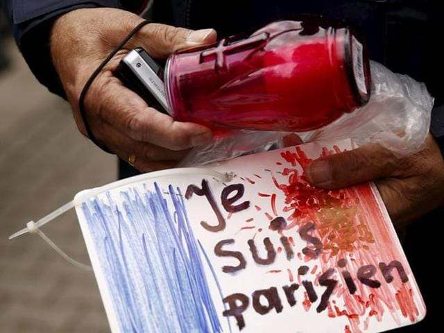 A man holds a candle and a drawing depicting the French flag and carrying the words