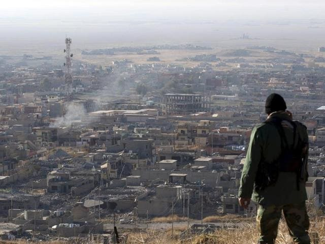 Iraqi autonomous Kurdish region's peshmerga forces and fighters from the Yazidi minority, a local Kurdish-speaking community which the Islamic State (IS) group had brutally targeted in the area, hold a Kurdish flag while entering the northern Iraqi town of Sinjar.