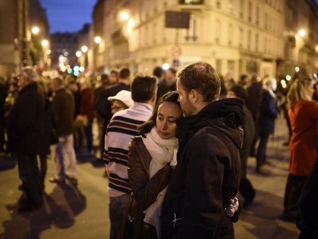 People take part in a gathering near Le Carillon restaurant, one of the site of the attacks in Paris.