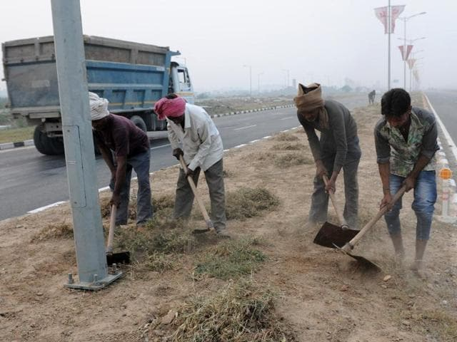 Workers giving finishing touches to the berms on the road connecting Kharar with Zirakpur in SAS Nagar on Sunday.