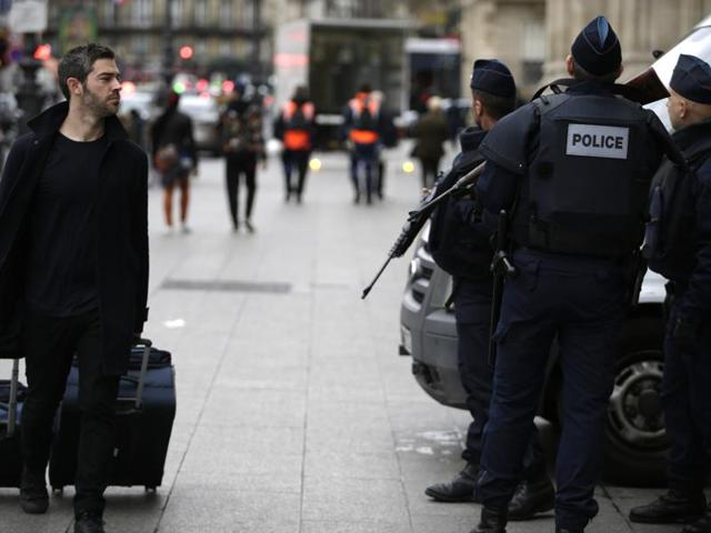 A traveller (L) walks past policemen standing guard outside the Gare du Nord railway station on November 16, 2015 in Paris.