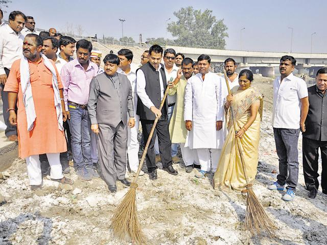 Municipal commissioner Abdul Samad and state women's commission member Rajdevi Chaudhary (with brooms) at the Hindon river bank on Sunday. Later, they were confronted by angry activists who said that the officials were trying to show that they were making efforts to clean the bank only for the cameras and they failed to do anything for months.